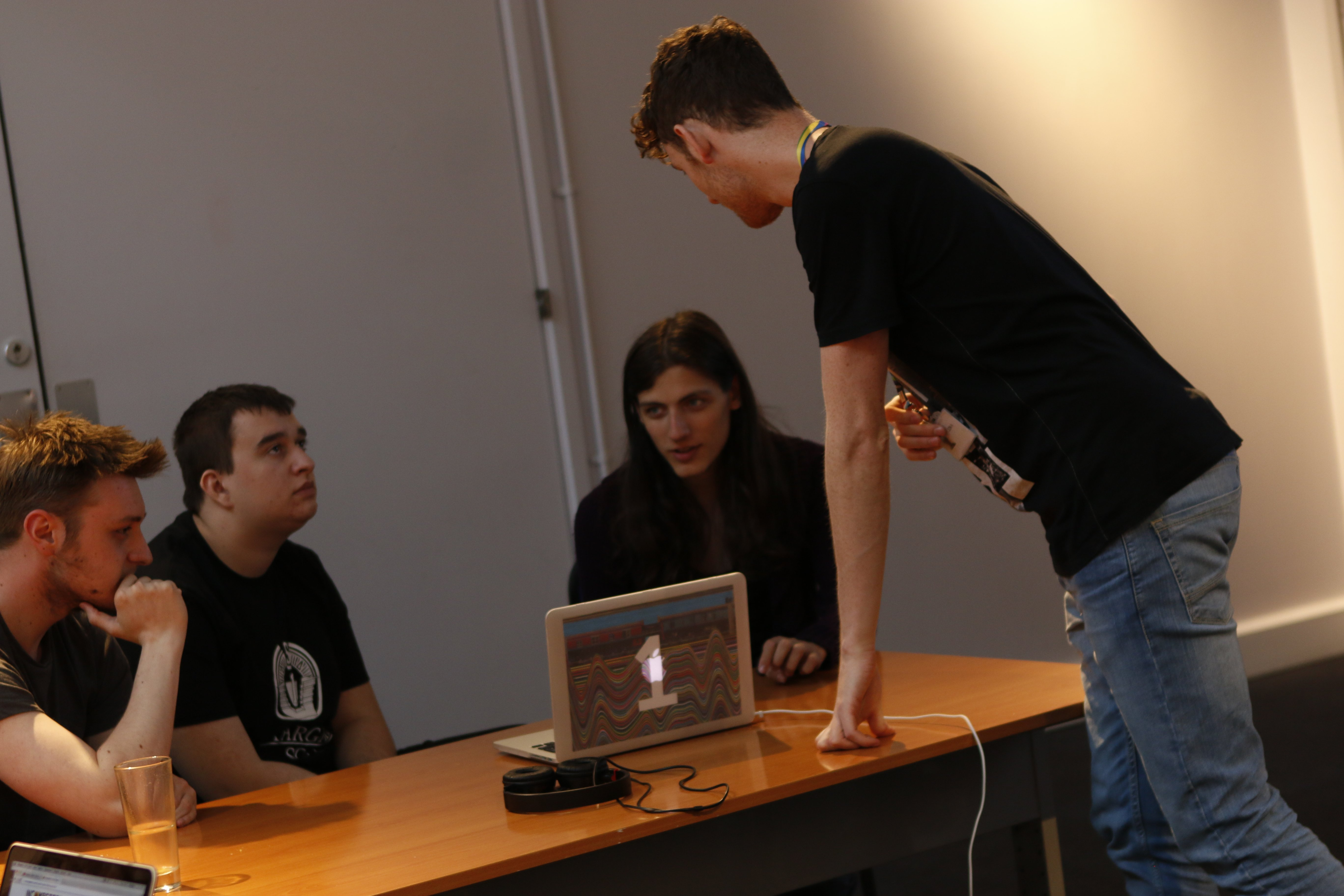 A group of young people sitting around a computer, as a staff member talks to them