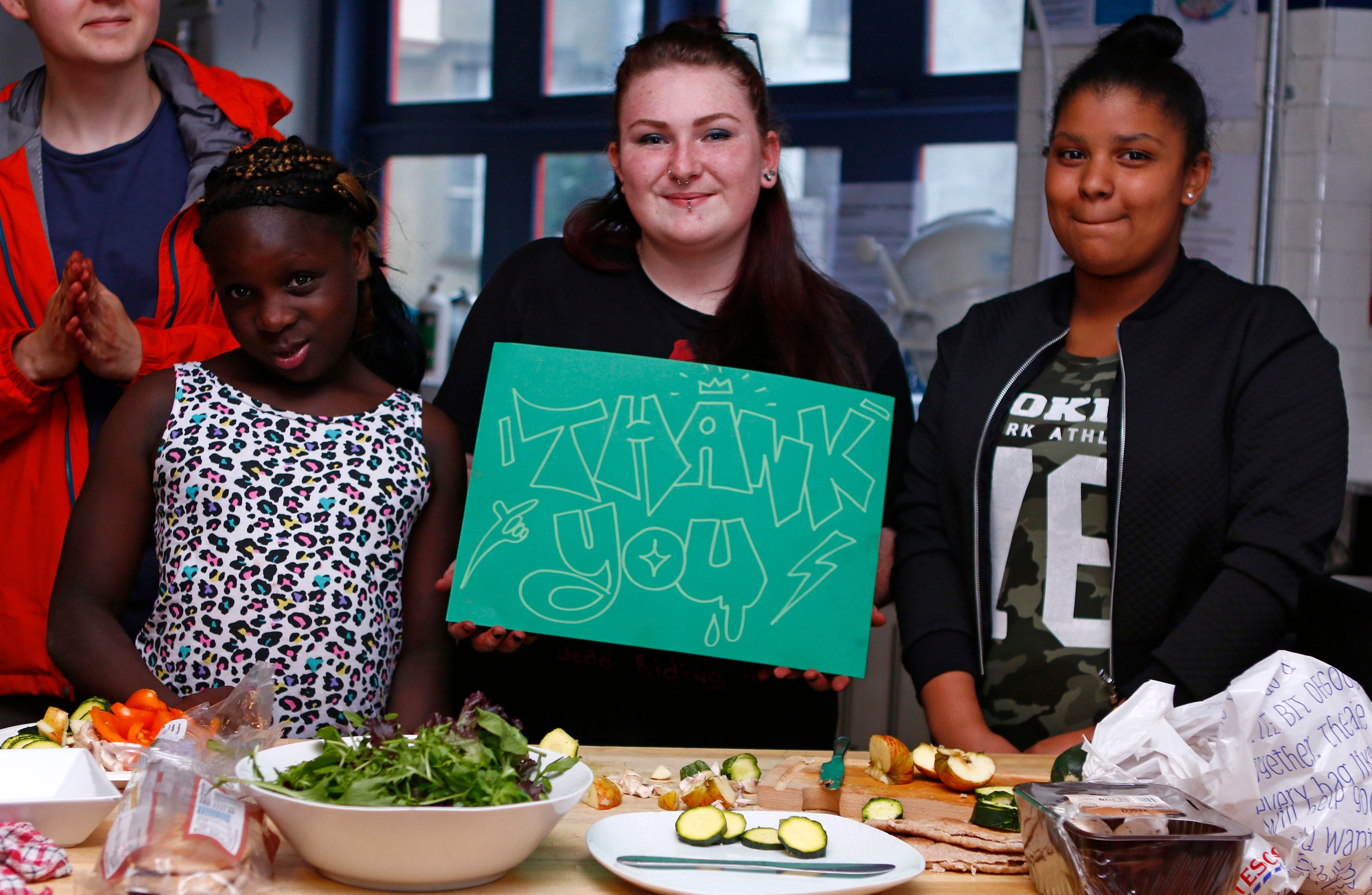 Three young women standing in a line in front of some food. One is holding up a Thank You sign