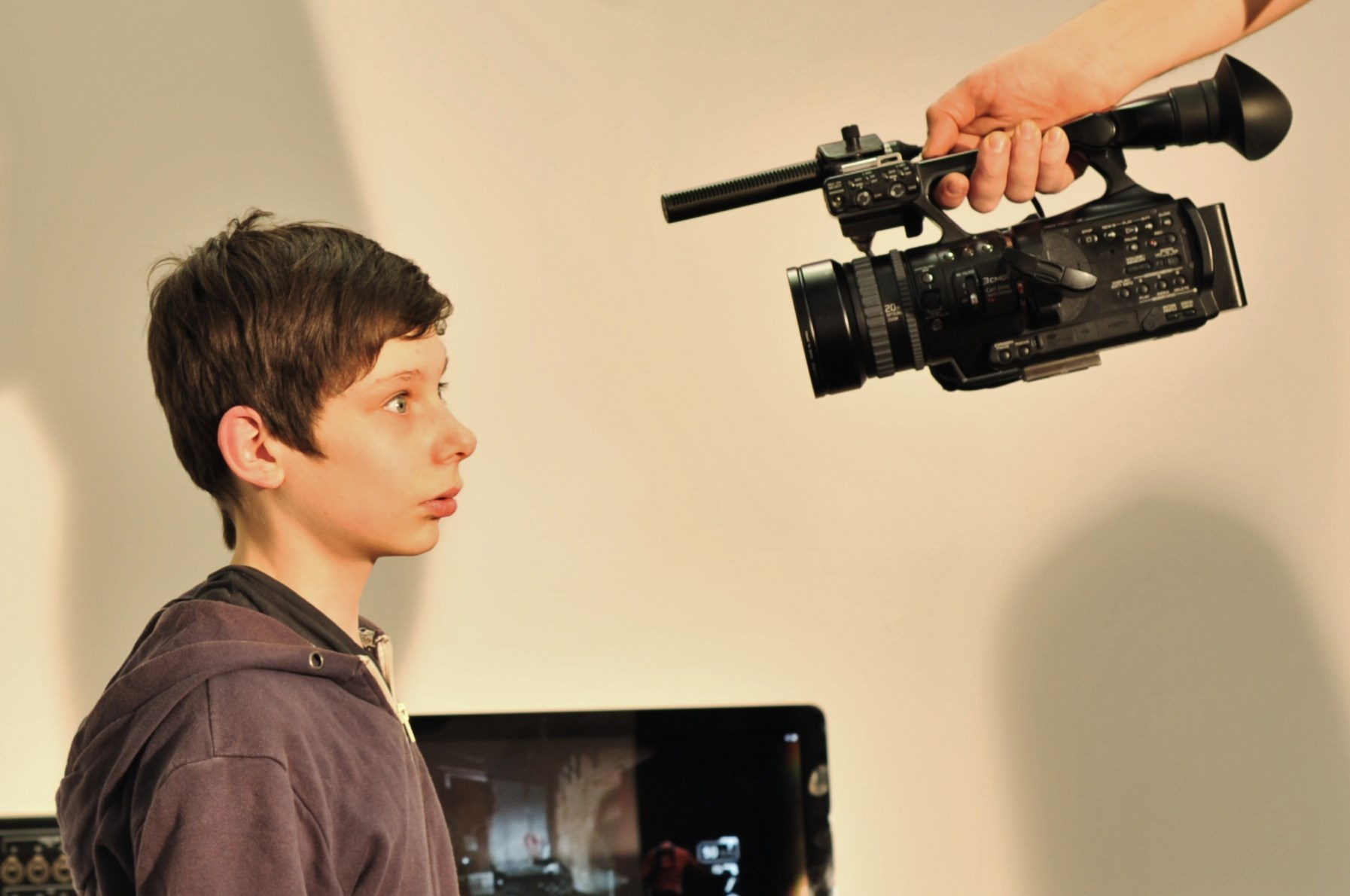 An alarmed looking young man, looking into a piece of recording equipment held by someone out of frame