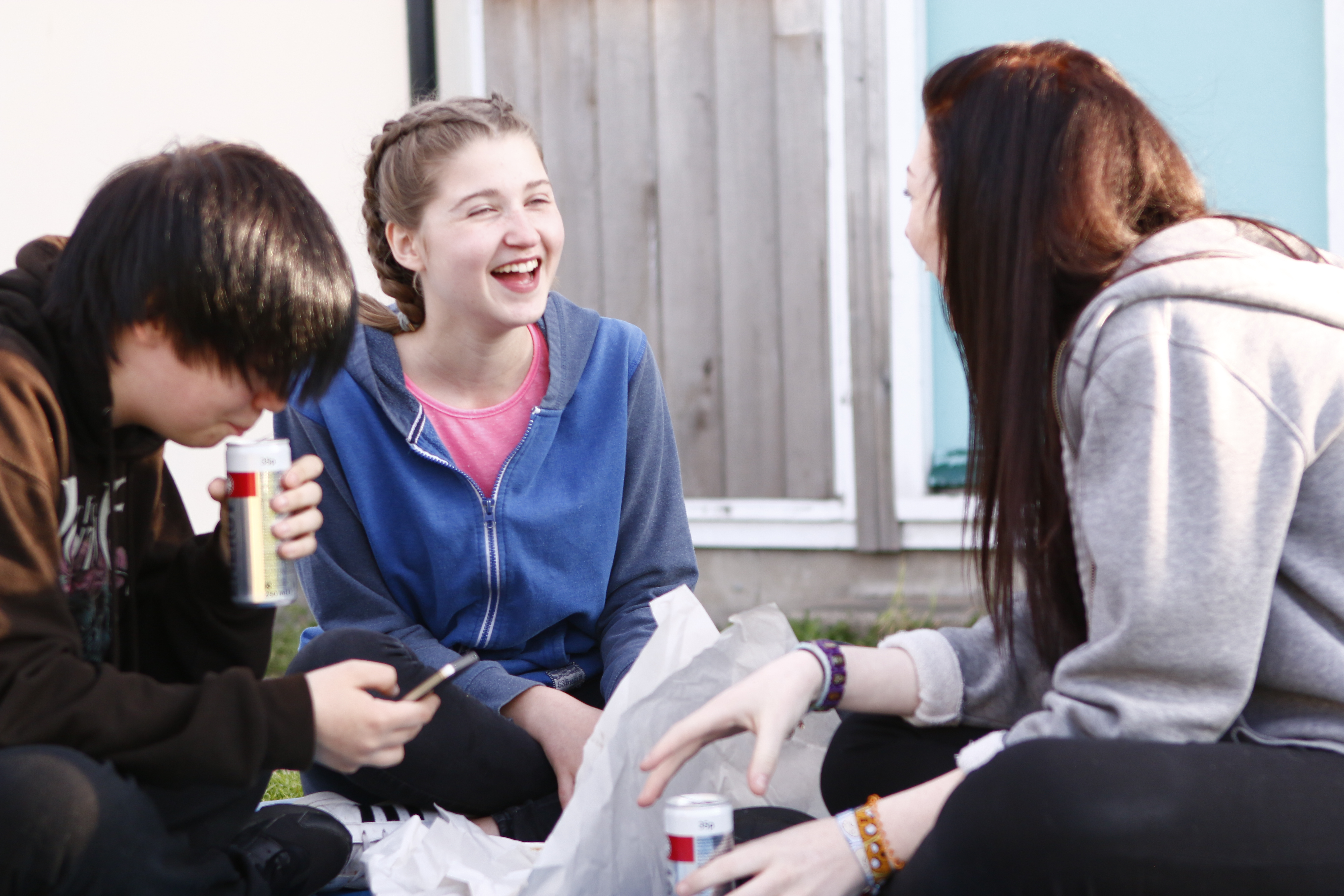Two girls laughing with each other, with a boy looking at his phone beside them