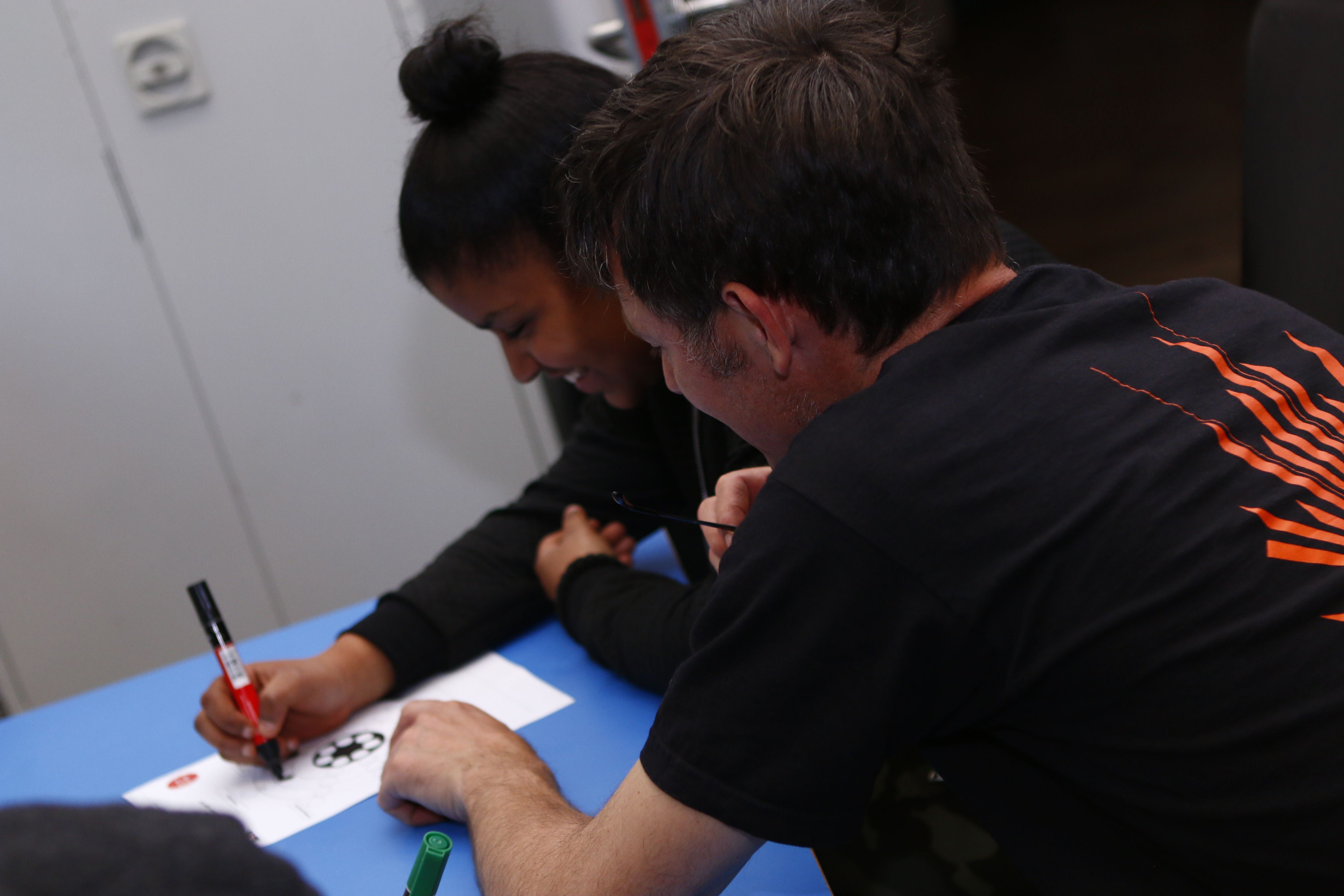 A member of staff helps a young woman to fill in paperwork