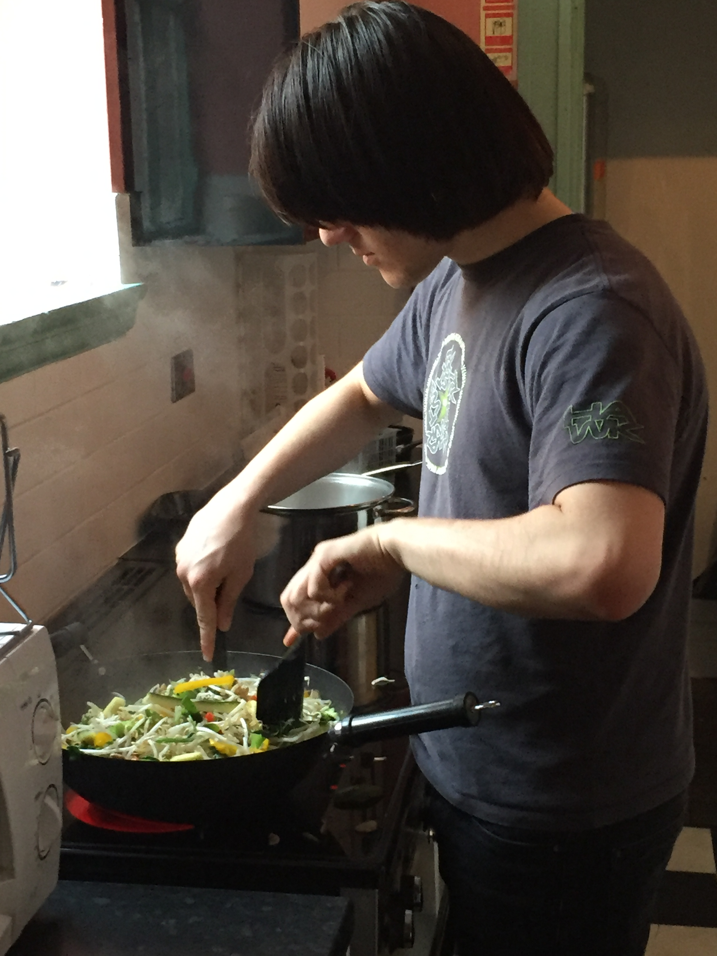 A young man cooking a stir fry