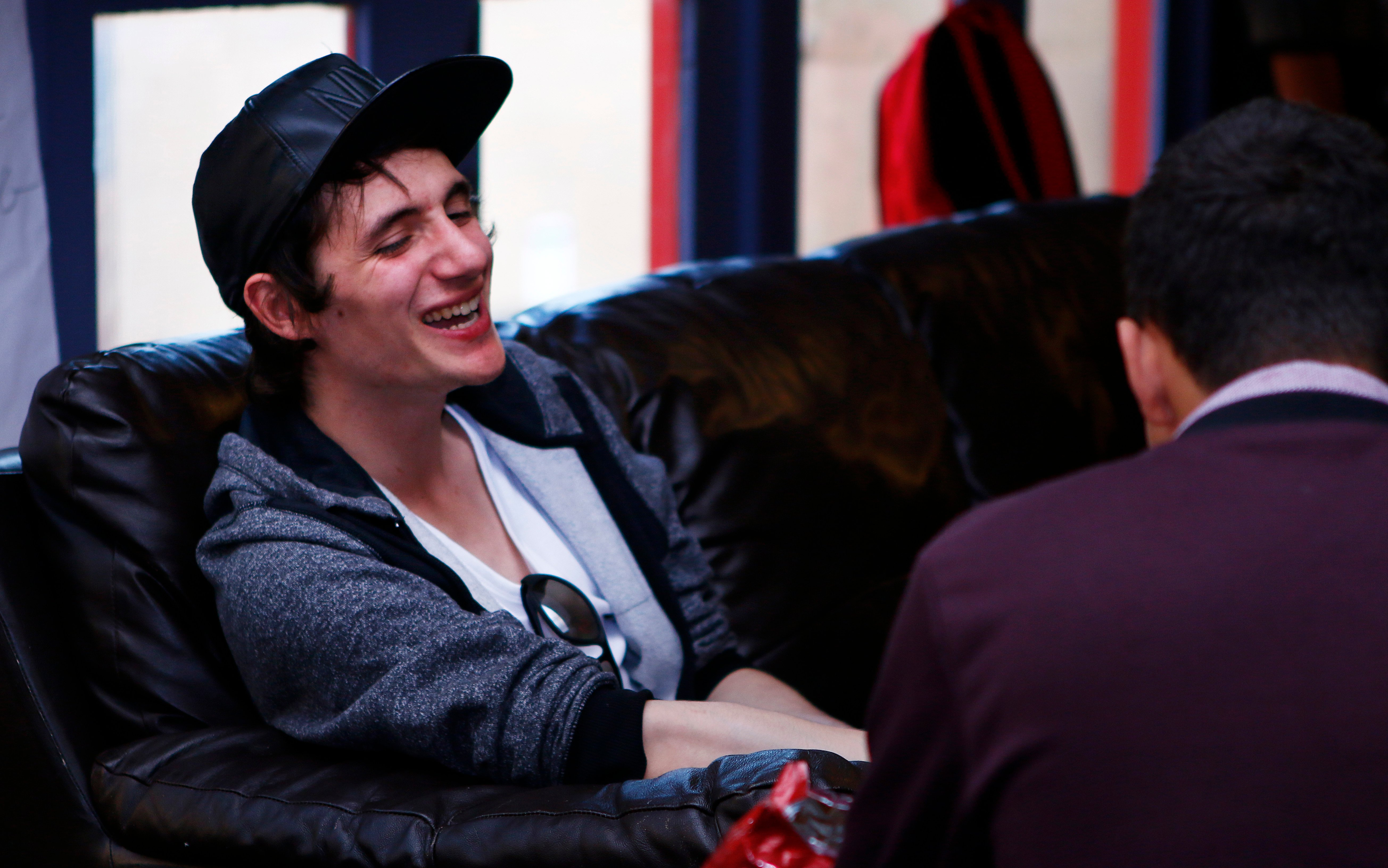 A happy young man sitting on a sofa, talking with someone facing away from the camera