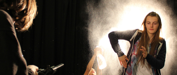 a young woman doing the robot in a cloud of spray, added by a young man sitting on the floor with a spray bottle