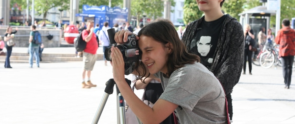 Two young people work a camera in the centre of Bristol