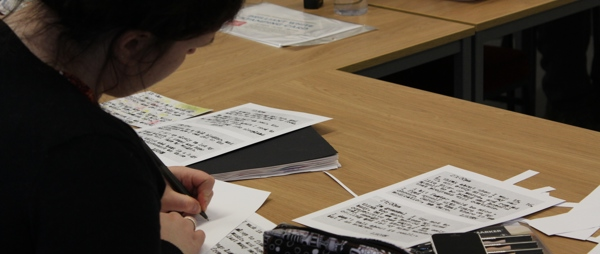 A young girl writing on card with typed words on it
