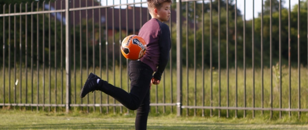 A boy kicking an orange football up into the air