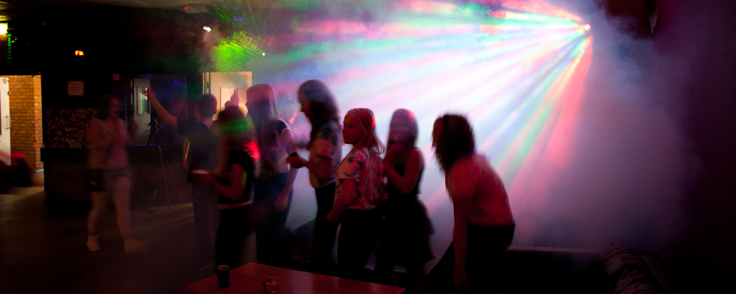 A group of young people dancing in a line, in a smoke filled room