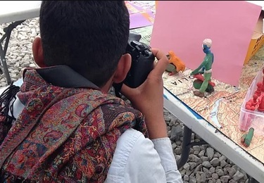 Young boy taking a photo of modelling clay depicting a man on a bike