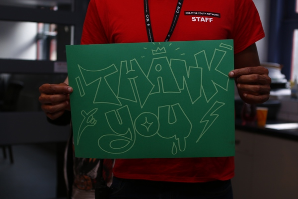 A staff member holding up a Thank You sign