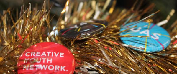 Badge pins intertwined with tinsel